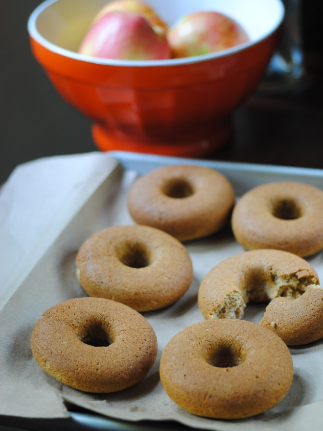 Gluten-free baked apple cider donuts taking a cooling break before getting brushed and sugared.